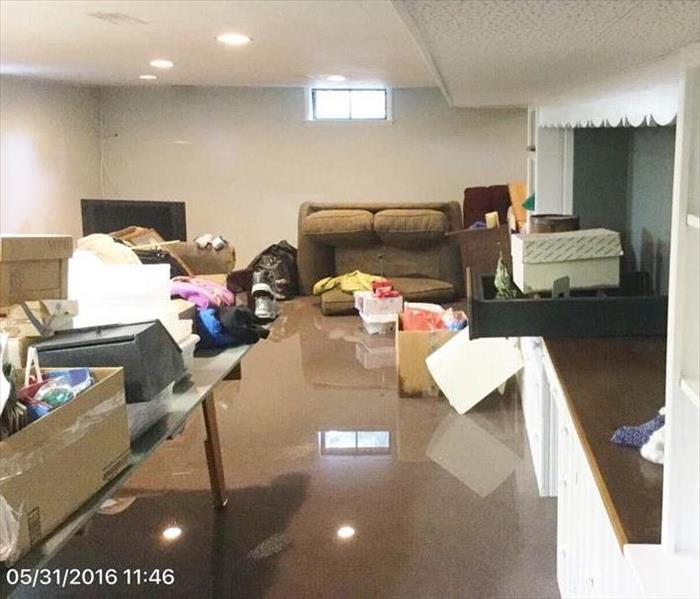 Basement with couch, cabinets, boxes and other contents surround by water