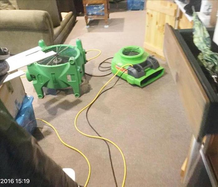 Air movers set on carpet with couch and furniture and contents around on the floor