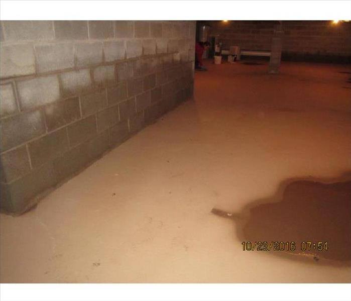 Layer of dry and wet mud on concrete basement floor