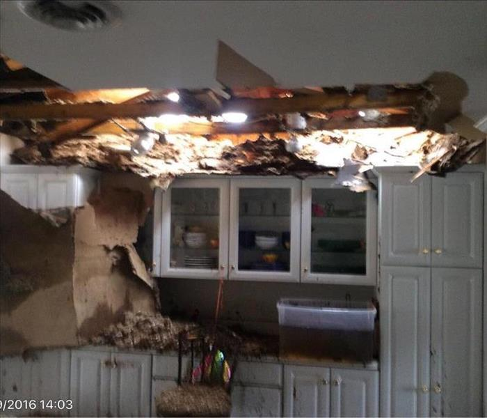 White kitchen with hole in the ceiling and large debris all over everything