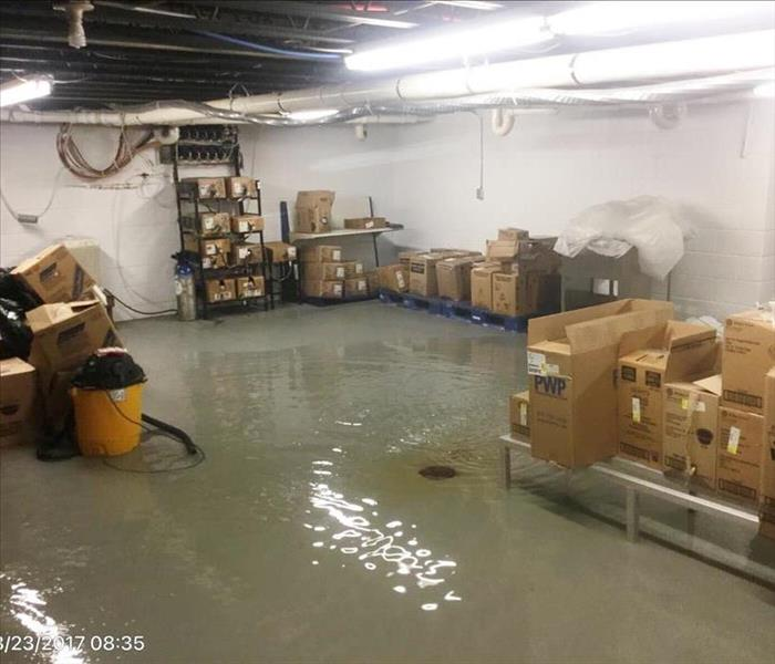 Gray and white basement with inches of water on the floor and boxes on shelving