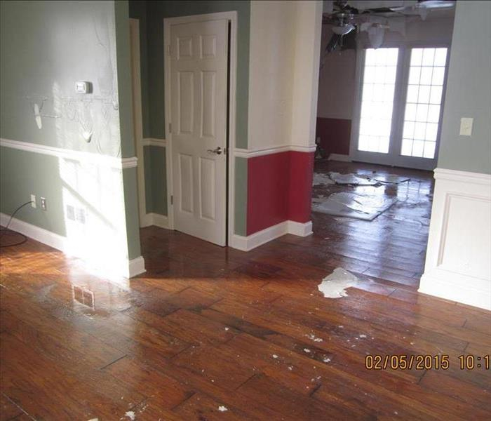 House with ceiling debris and water all over the hardwood floors