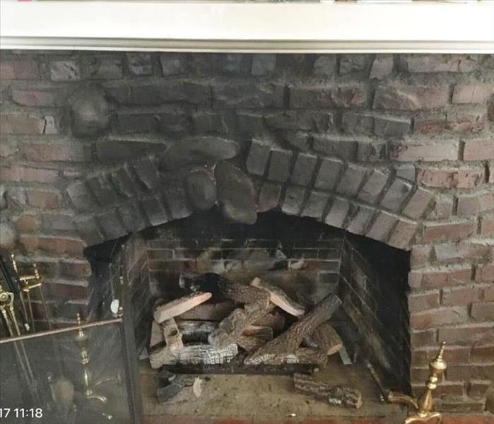 Dark brick fireplace with heavy black soot